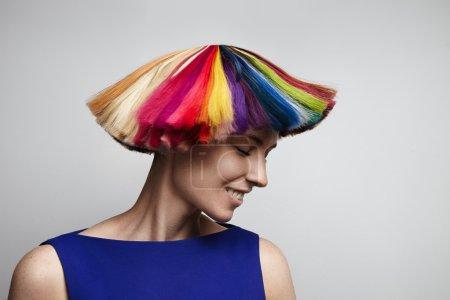 Photo pour Belle femme secouer cheveux arc-en-ciel coloré en studio sur fond blanc - image libre de droit