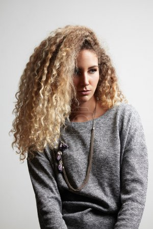 Photo pour Belle femme blonde aux cheveux bouclés sur fond gris - image libre de droit