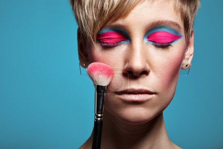 woman with bright makeup and closed eyes
