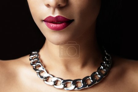 woman with red lips and silver necklace