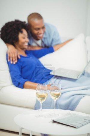 Happy couple on the sofa using laptop