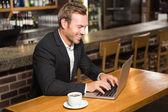 Pohledný muž pomocí přenosného počítače