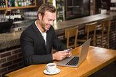Přemýšlivý muž pomocí notebooku a smartphone