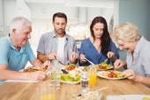 Rodina sedí u jídelního stolu s jídlem