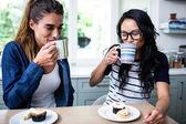 Kamarádky pití kávy u stolu