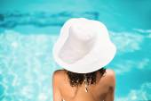 žena v bílém klobouku sedí u bazénu