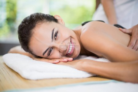 Woman smiling while receiving stone massage