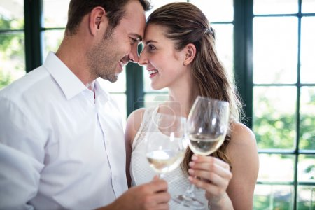 Couple toasting wine glasses in restaurant