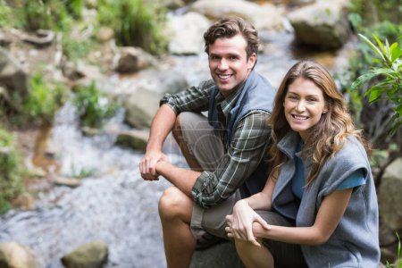 hikers sitting on rock by stream
