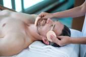 Muž přijímající masáž obličeje