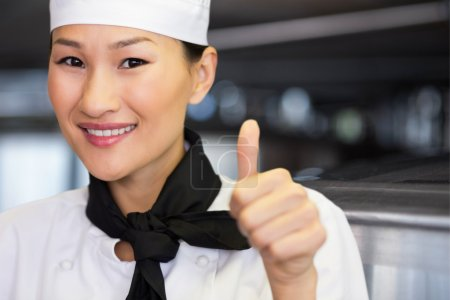 smiling female cook gesturing thumbs up