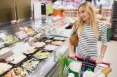 Žena hledá produkty v supermarketu