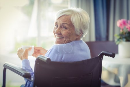 Happy senior woman on wheelchair holding a cup of tea