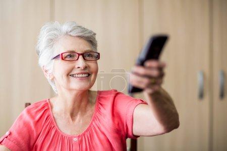 Senior woman using a remote control