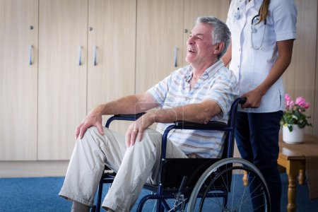 Female doctor carrying senior man on wheelchair