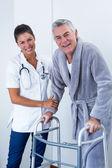 Portrét ženských lékaře pomáhá starší muž s walker