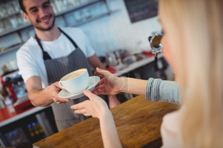 barista serving coffee to woman at cafe