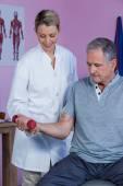 Fyzioterapeut, pomáhat starší muž zvednout činka