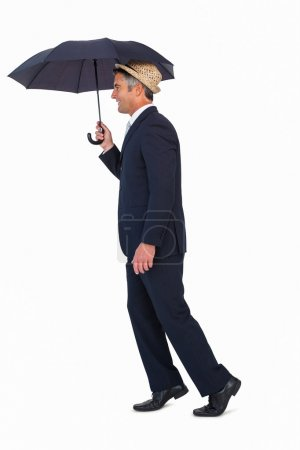 Businessman in straw hat under umbrella