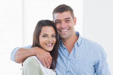 Loving couple smiling at home