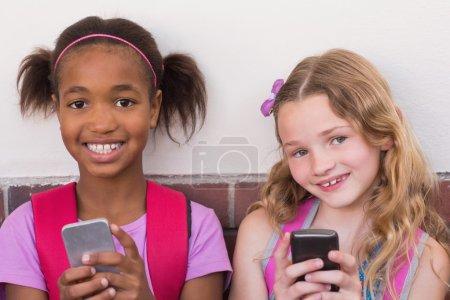 Cute pupils using mobile phone