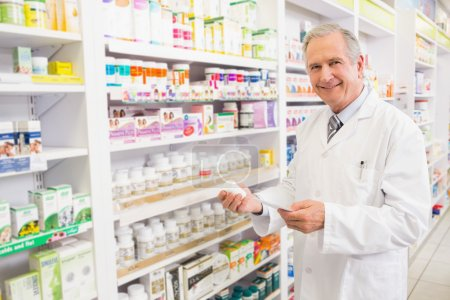Smiling senior pharmacist holding medicine and prescription