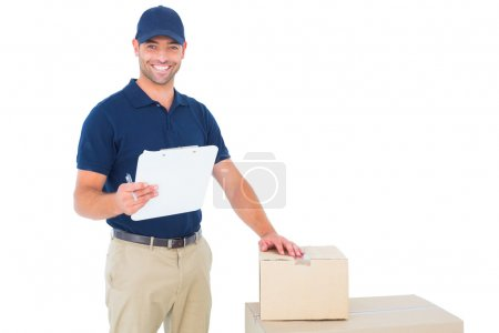 Delivery man with cardboard boxes and clipboard