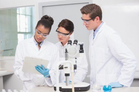 Scientists working with microscope and taking notes
