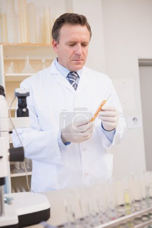 scientist looking at test tube with seeds