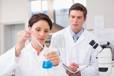 Scientists examining attentively pipette with fluid