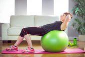 Přizpůsobit žena, která dělá sit ups na cvičení míč