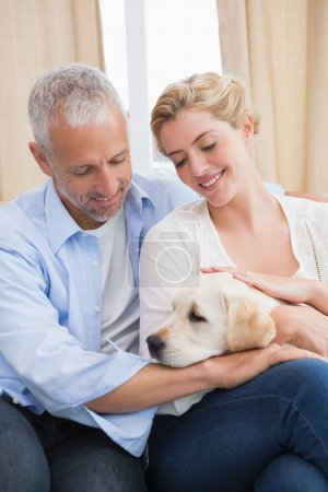 couple cuddling with puppy on sofa