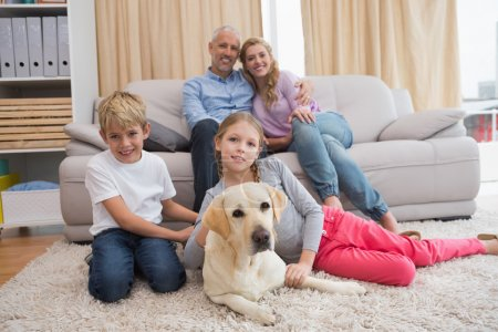 parents and children on sofa with labrador