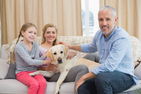 parents and daughter with labrador