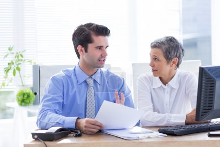 Two business people looking at a paper while working on folder