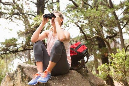 Blonde hiker sitting on rock