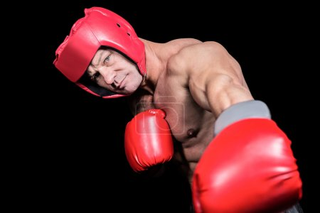 Portrait of boxer with gloves punching against black background
