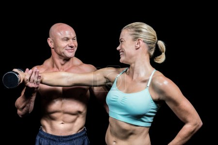 Cheerful trainer helping woman for lifting dumbbell
