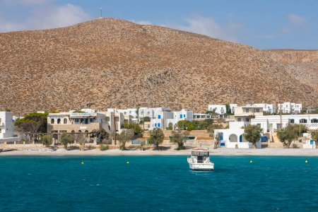 Photo for Folegandros Island, Greece - 24 September 2020: View of the small port town on the island of Folegandros. White villas on the hill of the island, boat in the waters of the bay. - Royalty Free Image