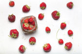 Spousta čerstvé světlé červené jahody na světlém pozadí