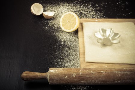 Photo for Set for home baking on a black background with flour. Rolling pin, dough, half of lemon, baking form, eggshell. Toned. - Royalty Free Image