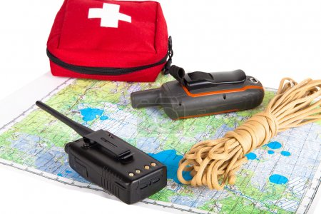 Map, gps navigator, portable radio, rope and first aid kit on a