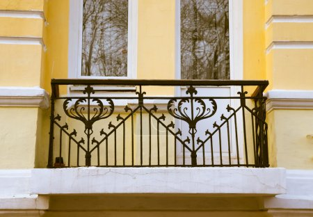 Iron balcony on the yellow plastering wall. Toned