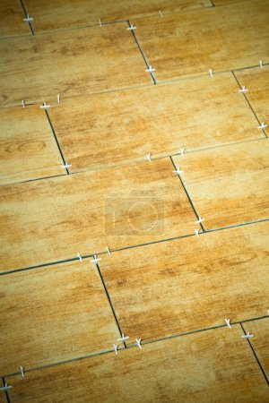 Laying ceramic tiles on a special cement grout. Selective focus.