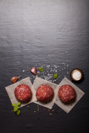 Raw ground beef meat steak cutlets with herbs and spices on blac