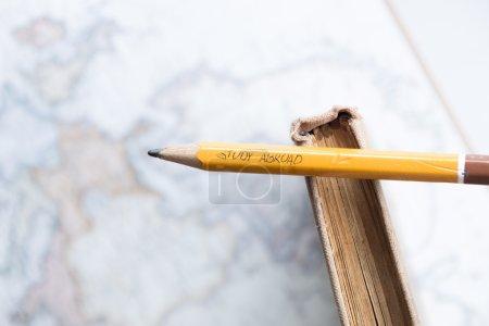 """Photo pour Étude à l """"étranger - inscription au crayon, carte et livre - image libre de droit"""