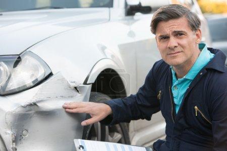 Kfz-Mechaniker inspizieren Schäden am Auto und füllen sie aus