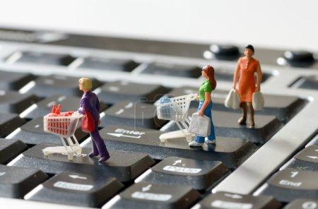 Photo pour Acheteurs miniatures avec panier sur un clavier d'ordinateur - image libre de droit