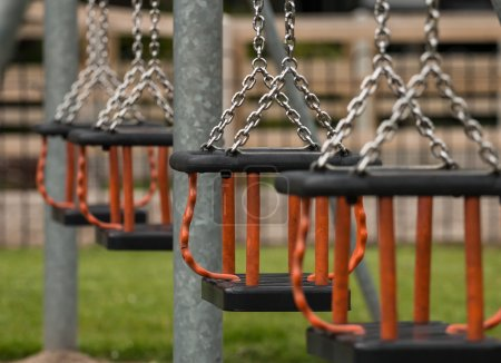 Photo for Row of swing seats at a local play park or children's playground provided by the local council for children to have fun in their community. Selective focus on a single Cradle seat. - Royalty Free Image