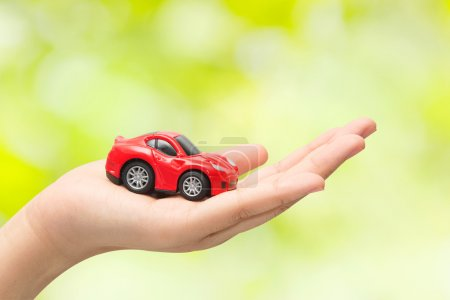 hand holding the model of car on green background. symbol photo